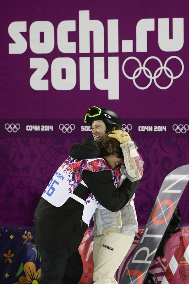 Photo - Switzerland's Iouri Podladtchikov, left, celebrates with Shaun White, of the United States, after Podladtchikov won the gold medal in the men's snowboard halfpipe final at the Rosa Khutor Extreme Park, at the 2014 Winter Olympics, Tuesday, Feb. 11, 2014, in Krasnaya Polyana, Russia. (AP Photo/Jae C. Hong)