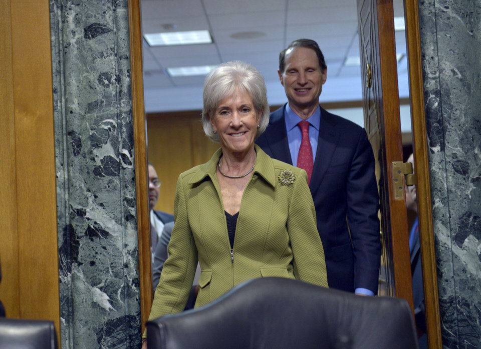 Photo - Health and Human Services Secretary Kathleen Sebelius, followed by Senate Finance Committee Chairman Sen. Ron Wyden, D-Ore., arrives on Capitol Hill in Washington, Thursday, April 10, 2014, to testify before the committee's hearing on the HHS Department's fiscal Year 2015 budget. Sebelius said 7.5 million Americans have now signed up for health coverage under President Barack Obama's health care law. That's a 400,000 increase from the 7.1 million that Obama announced last week at the end of the law's open enrollment period. The figure exceeded expectations, a surprise election-year success for the law after a disastrous roll-out.   (AP Photo/Susan Walsh)