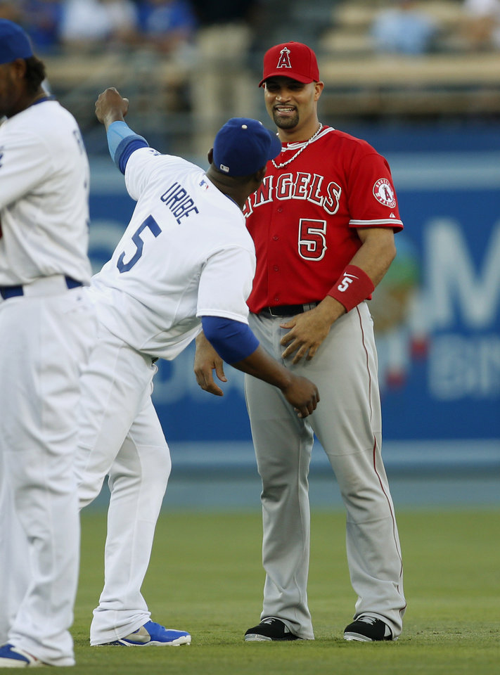 Photo - Los Angeles Angels' Albert Pujols, right, and Los Angeles Dodgers' Juan Uribe, left, speak before a baseball game, Monday, August 4, 2014, in Los Angeles. (AP Photo/Danny Moloshok)
