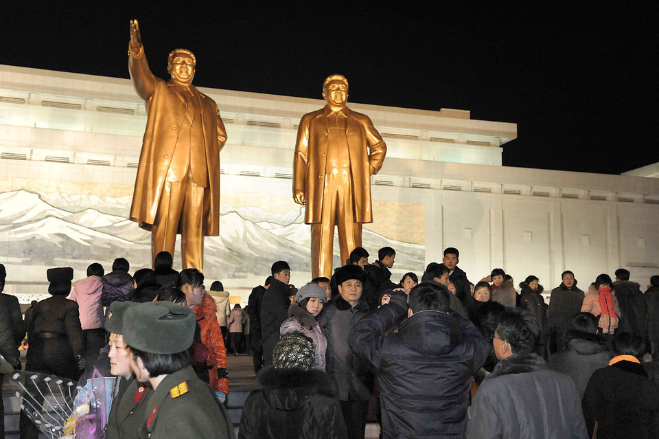 Photo - North Koreans visit giant statues of their late leaders Kim Il Sung, left, and Kim Jong Il at Mansu Hill as they celebrate the New Year in Pyongyang, North Korea, early Tuesday, Jan. 1, 2013. North Korean leader Kim Jong Un on Tuesday called for improving the economy and living standards of his impoverished nation with the same urgency that scientists showed in successfully testing a long-range rocket recently. (AP Photo/Kyodo News) JAPAN OUT, MANDATORY CREDIT, NO LICENSING IN CHINA, HONG KONG, JAPAN, SOUTH KOREA AND FRANCE