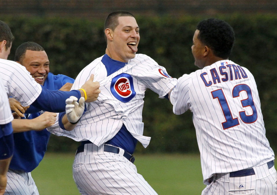 Chicago Cubs' Starlin Castro, right, and teammates mob Bryan LaHair after LaHair hit the game-winning single off Houston Astros relief pitcher Hector Ambriz during the ninth inning of a baseball game Wednesday, Oct. 3, 2012, in Chicago. The Cubs won 5-4. (AP Photo/Charles Rex Arbogast)