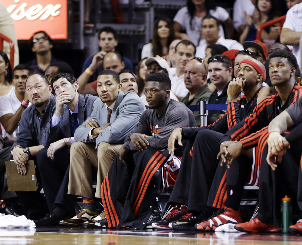 From left, Chicago Bulls\' Kirk Hinrich, Derrick Rose, Nate Robinson, Richard Hamilton and Jimmy Butler watch from the bench during the final seconds of Game 2 of their NBA basketball playoff series in the Eastern Conference semifinals against the Miami Heat, Wednesday, May 8, 2013, in Miami. The Heat won 115-78. (AP Photo/Lynne Sladky)
