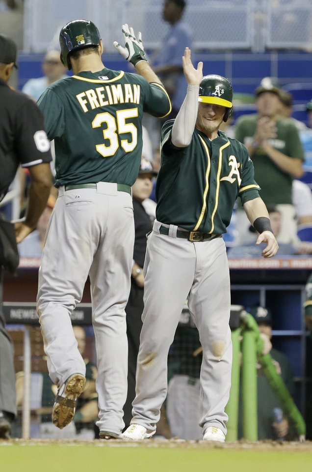 Photo - Oakland Athletics' Nate Freiman (35) is congratulated by Josh Donaldson after Freiman hit a three-run home run scoring Donaldson and Yoenis Cespedes during the sixth inning of a baseball game against the Miami Marlins, Sunday, June 29, 2014 in Miami. The Athletics defeated the Marlins 4-3. (AP Photo/Wilfredo Lee)