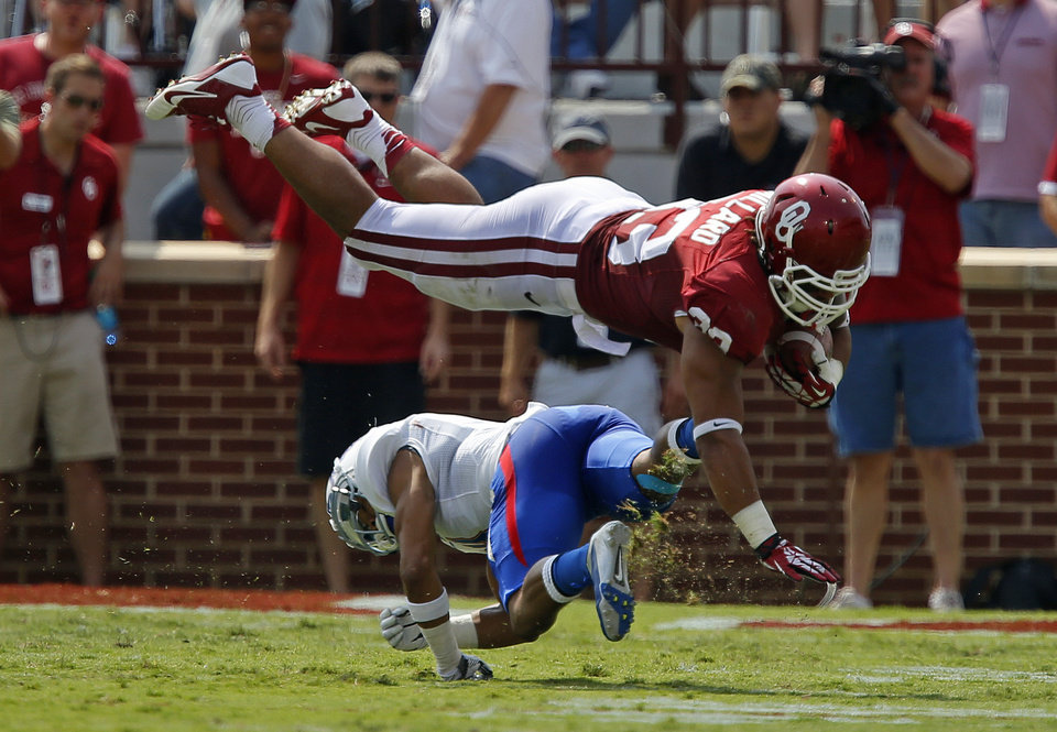 Photo - Oklahoma's Trey Millard (33) leaps over Tulsa's Darnell Walker (4) during a college football game between the University of Oklahoma Sooners (OU) and the Tulsa Golden Hurricane at Gaylord Family-Oklahoma Memorial Stadium in Norman, Okla., on Saturday, Sept. 14, 2013. Oklahoma won 51-20. Photo by Bryan Terry, The Oklahoman