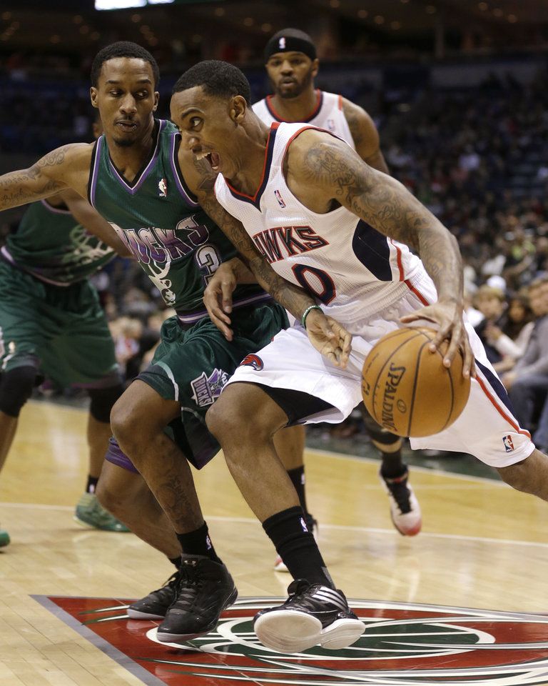 Atlanta Hawks' Jeff Teague (0) drives against Milwaukee Bucks' Brandon Jennings, left, during the first half of an NBA basketball game, Saturday, Feb. 23, 2013, in Milwaukee. (AP Photo/Jeffrey Phelps)