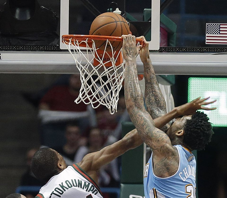 Photo - Denver Nuggets' Wilson Chandler, right, dunks on the Milwaukee Bucks' Giannis Antetokounmpo during the second half of an NBA basketball game Thursday, Feb. 20, 2014, in Milwaukee. (AP Photo/Jeffrey Phelps)
