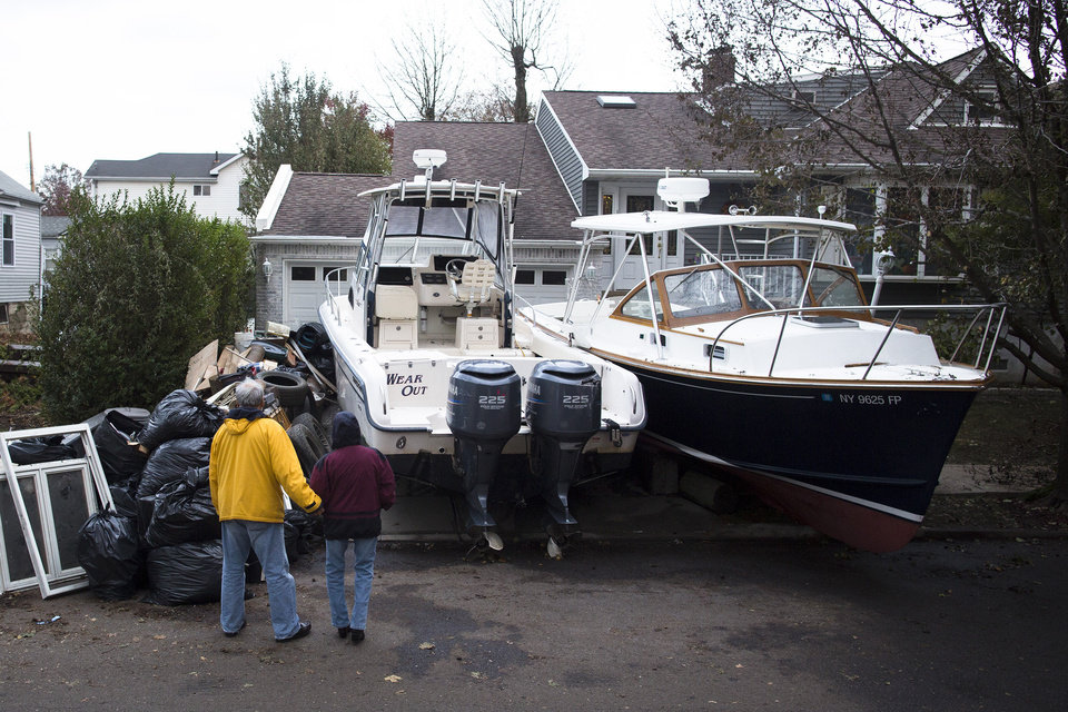 Two onlookers hold hands beside two boats that were driven inland by flood waters, Wednesday, Oct. 31, 2012, in New York.  Sandy, the storm that made landfall Monday, caused multiple fatalities, halted mass transit and cut power to more than 6 million homes and businesses. (AP Photo/ John Minchillo) ORG XMIT: NYJM119