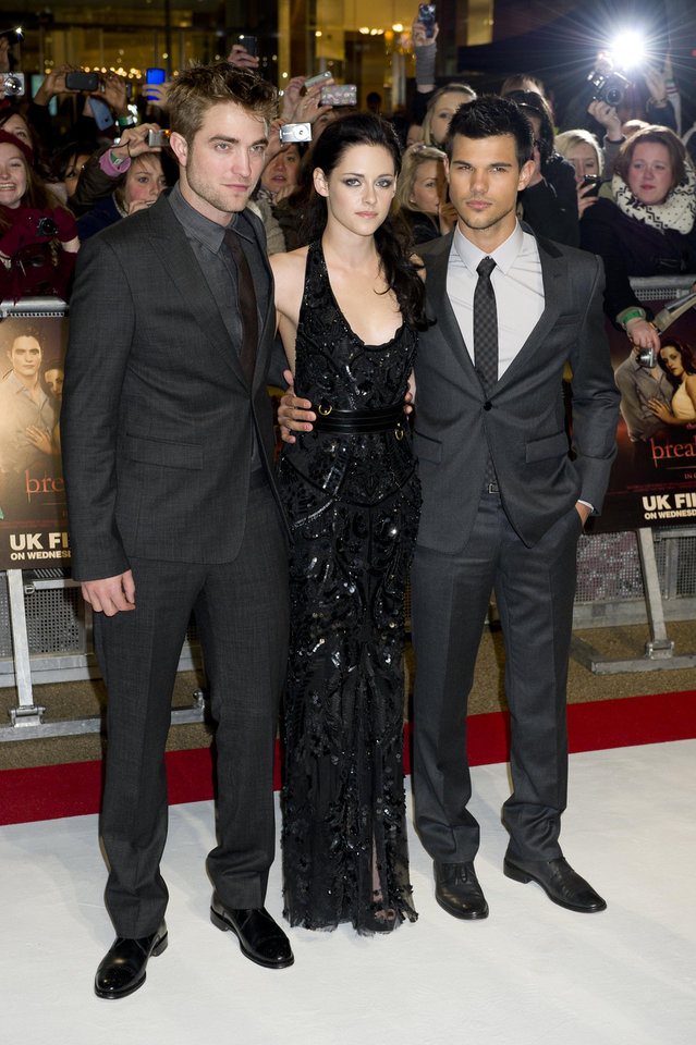 British actor Robert Pattinson, left, US actress Kristen Stewart, centre and US actor Taylor Lautner arrive for the UK premiere of 'Twilight Breaking Dawn Part 1' at a central London venue,  Wednesday, Nov. 16, 2011. (AP Photo/Jonathan Short) ORG XMIT: LJS101