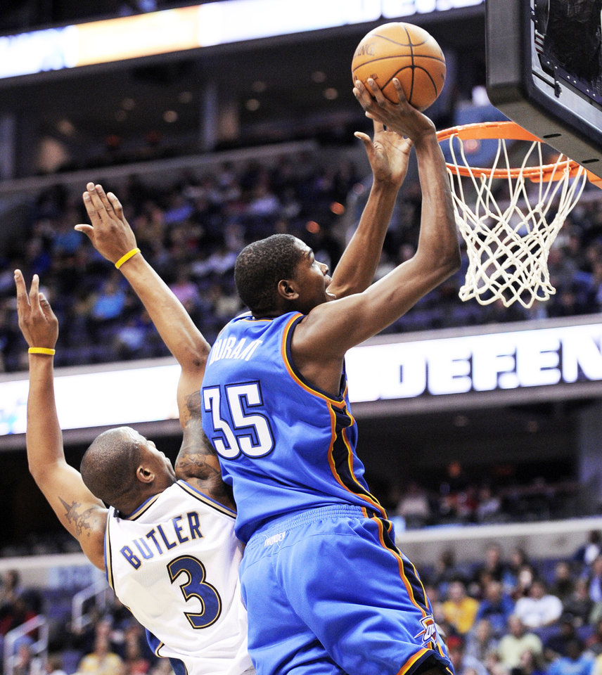 Photo - OKC's Kevin Durant, right, goes to the basket against Washington forward Caron Butler during action on Tuesday in Washington. The Thunder beat the Wizards 110-98.  AP photo