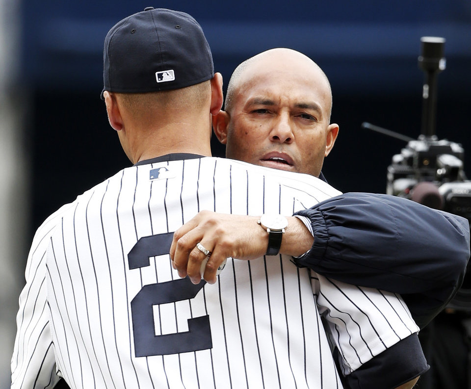 Photo - Former New York Yankees relief pitcher Mariano Rivera embraces New York Yankees Derek Jeter, left, after throwing out the ceremonial first pitch to Jeter before a baseball game, the Yankees home opener against the Baltimore Orioles, at Yankee Stadium in New York, Monday, April 7, 2014. (AP Photo/Kathy Willens)