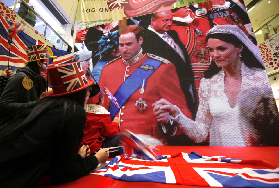 Photo - Hong Kong residents sit next to a giant TV screen showing the live broadcast of Britain's Prince William and Kate Middleton at Westminster Abbey for the Royal Wedding at a shopping mall in Hong Kong Friday, April 29, 2011.  (AP Photo/Kin Cheung) ORG XMIT: XKC111