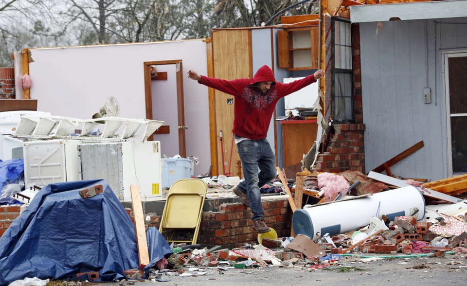 Photo - Jay Aycock, 33, of Petal, Miss., leaps from the raised floor of what remains of his aunt's kitchen to the ground Tuesday, Feb. 12, 2013 following the Sunday afternoon tornado that caused damage throughout the community. Aycock, who helped his aunt recover some of her personal items, was not affected by the tornado. (AP Photo/Rogelio V. Solis)