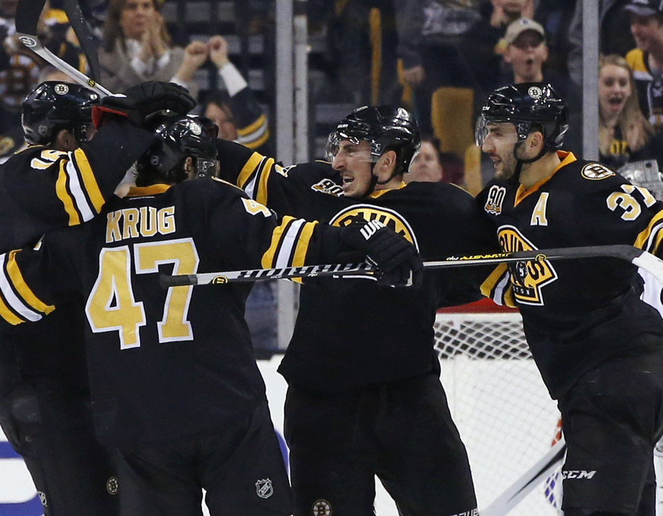 Photo - Boston Bruins left wing Brad Marchand, center, celebrates his game-winning goal against the Los Angeles Kings with teammates Torey Krug (47) and Patrice Bergeron (37) during the third period of an NHL hockey game in Boston, Monday, Jan. 20, 2014. The Bruins won 3-2. (AP Photo/Elise Amendola)