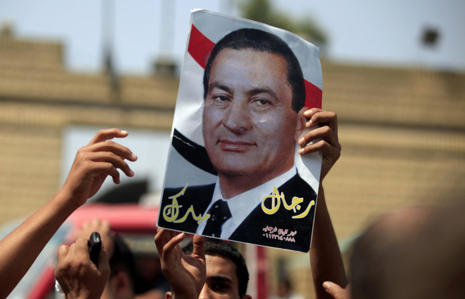 Photo - A supporter of Egypt's deposed autocrat Hosni Mubarak holds a poster of him and chants slogans in front of Tora prison, where Mubarak has been held, in Cairo, Thursday, Aug. 22, 2013. Mubarak has been released from jail and taken to military hospital in Cairo. The Arabic writing on the poster reads