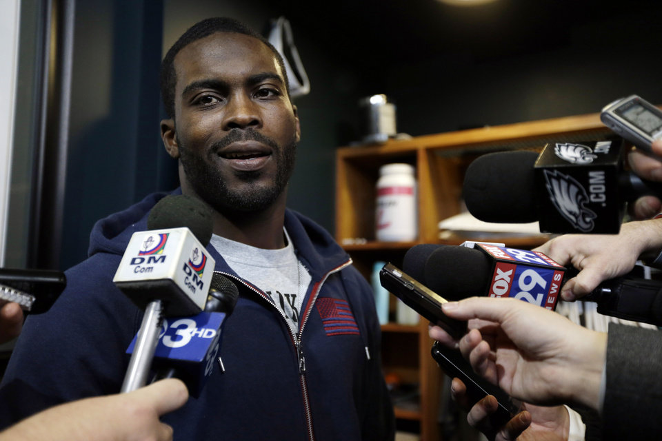 FILE - In this Dec. 31, 2012 file photo, Philadelphia Eagles quarterback Michael Vick speaks to members of the media as he cleans out his locker at the team's NFL football training facility in Philadelphia. Vick, who was slated to earn $16 million next season, has agreed to a restructured deal with the Eagles. Vick, who was injured and inconsistent last season, eventually giving way to rookie Nick Foles, now has a three-year contract, and will compete with Foles to see who runs new coach Chip Kelly's offense this season. (AP Photo/Matt Rourke, File)