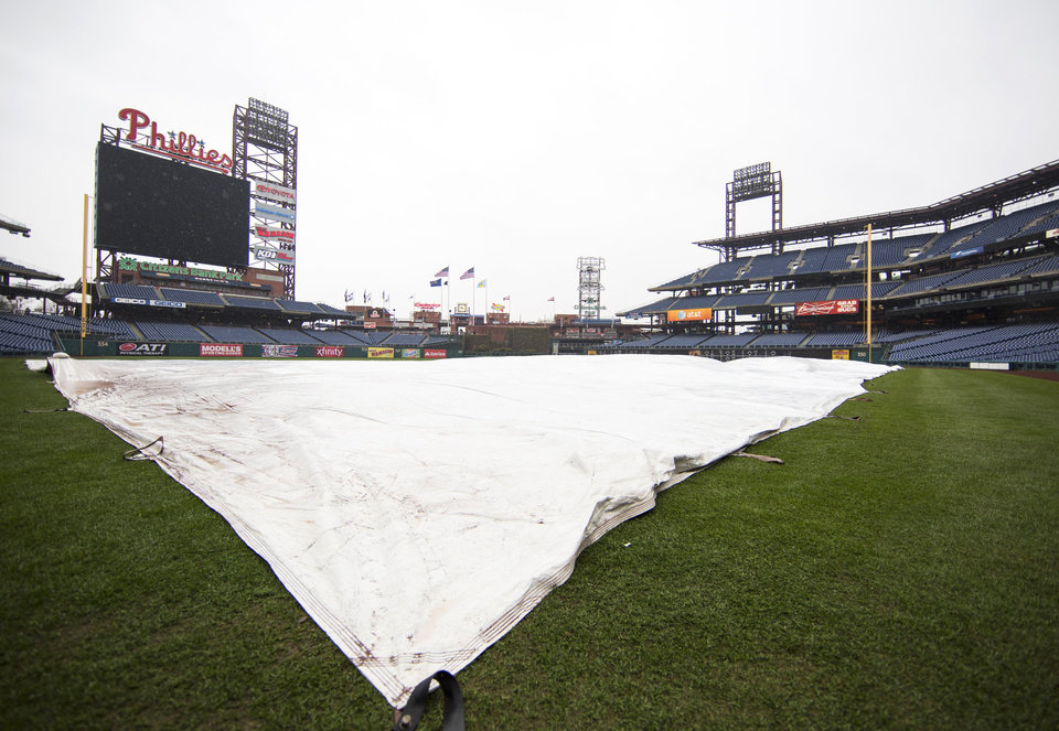 Photo - The tarp covers the field as the exhibition baseball game between the Pittsburgh Pirates and the Philadelphia Phillies is canceled due to rain, Saturday, March 29, 2014, in Philadelphia. (AP Photo/Chris Szagola)