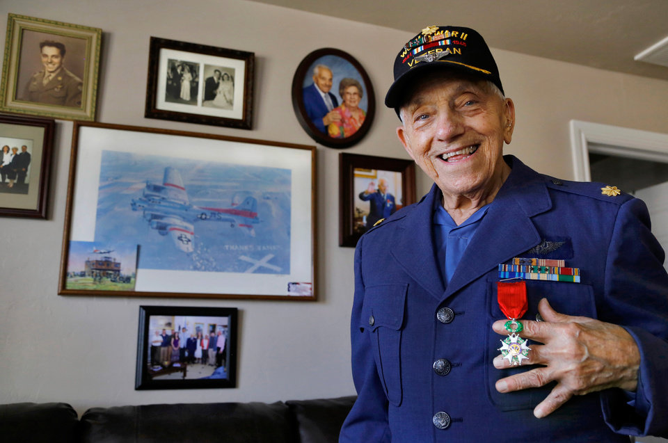 Photo -  Pete Durso, a World War II veteran who was a member of a B-17 crew, shows off the French Legion of Honor award he recently received. A wall in his southwest Oklahoma City apartment is adorned with photos of his military days.[Photo by Jim Beckel, The Oklahoman]
