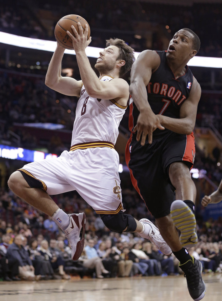 Photo - Cleveland Cavaliers' Matthew Dellavedova (8), from Australia, jumps to the basket as Toronto Raptors' Kyle Lowry (7) defends during the fourth quarter of an NBA basketball game Tuesday, March 25, 2014, in Cleveland. Cleveland defeated Toronto 102-100. (AP Photo/Tony Dejak)