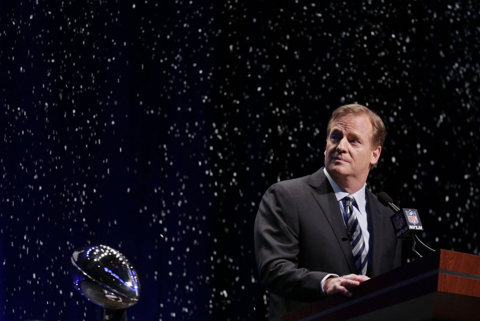 Photo - NFL comissioner Roger Goodell looks at artificial snow falls on stage as he speaks at a news conference Friday, Jan. 31, 2014, in New York. The Seattle Seahawks are scheduled to play the Denver Broncos in the NFL Super Bowl XLVIII football game on Sunday, Feb. 2, at MetLife Stadium in East Rutherford, N.J. (AP Photo/Charlie Riedel)