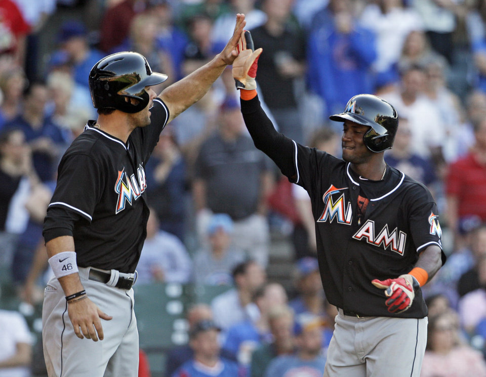 Photo - Miami Marlins' Garrett Jones, left, and Adeiny Hechavarria celebrate after scoring on a two-run single hit by Reed Johnson during the ninth inning of a baseball game against the Chicago Cubs in Chicago, Friday, June 6, 2014. (AP Photo/Nam Y. Huh)