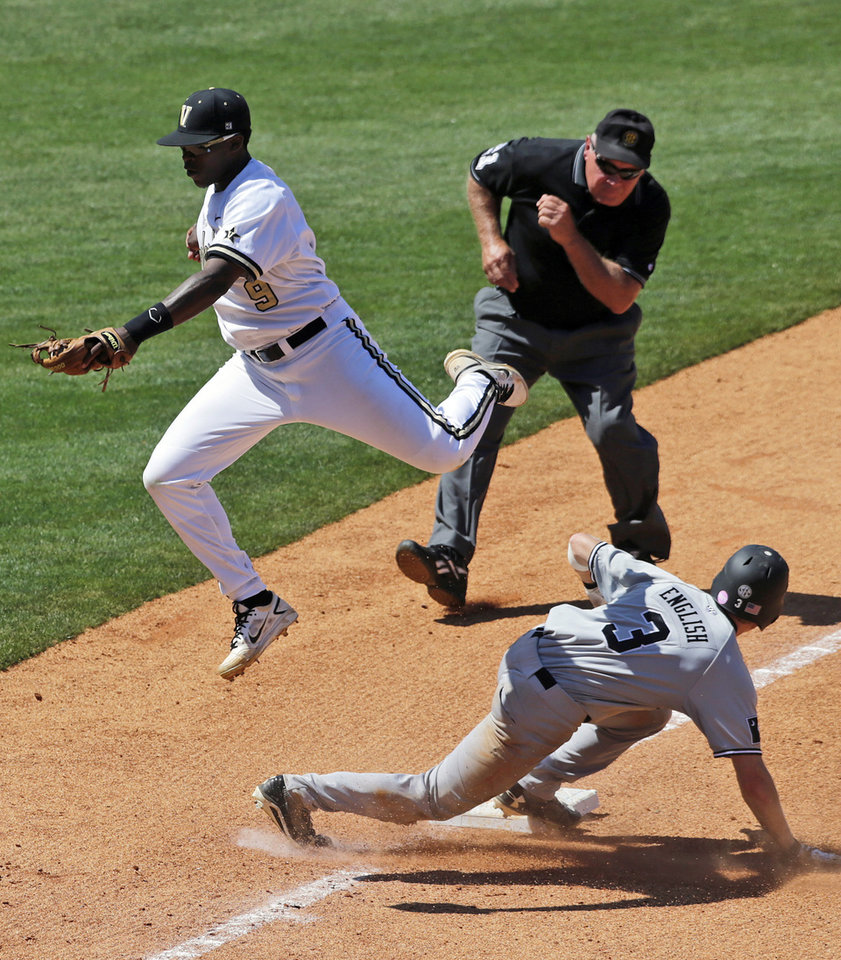 Photo - South Carolina's Tanner English (3) steals third base as Vanderbilt's Xavier Turner takes the high throw in the sixth inning of a Southeastern Conference tournament baseball college game at the Hoover Met in Hoover, Ala., Thursday, May 23, 2013. (AP Photo/Dave Martin)