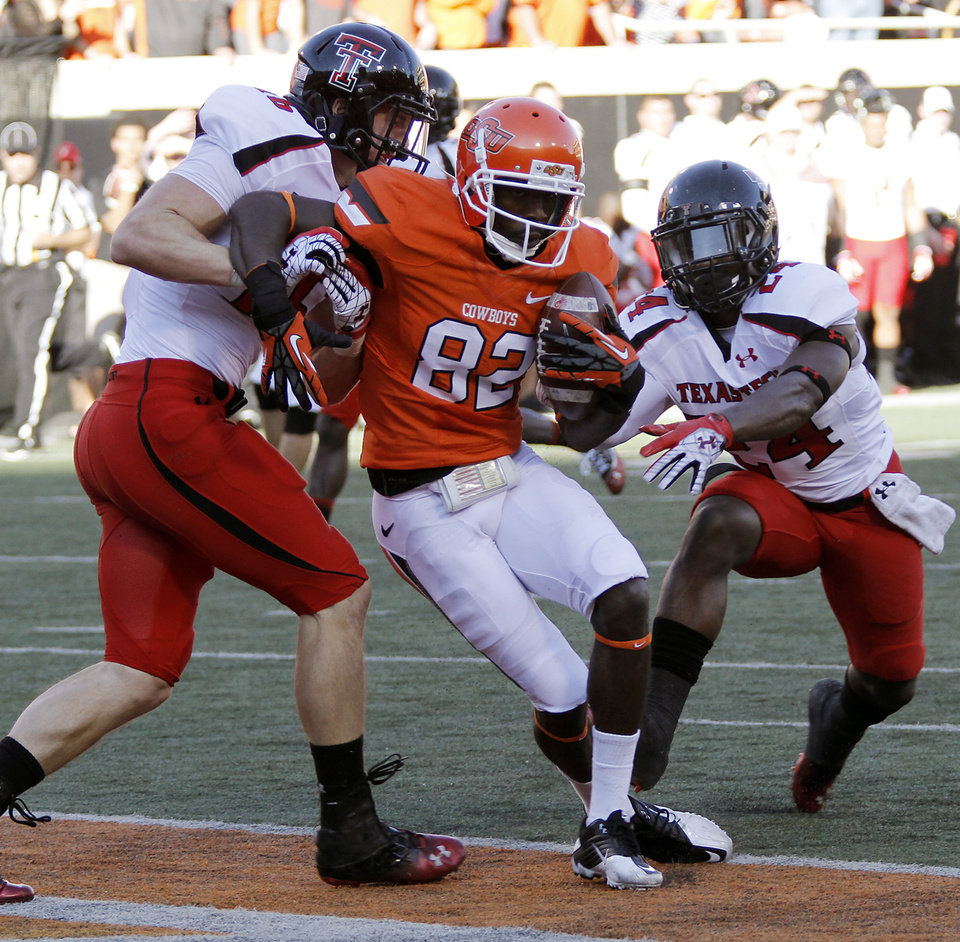 Photo - Oklahoma State's Isaiah Anderson (82) makes a touchdown catch between Texas Tech's Cody Davis (16) and Bruce Jones (24) during the college football game between the Oklahoma State University Cowboys (OSU) and Texas Tech University Red Raiders (TTU) at Boone Pickens Stadium on Saturday, Nov. 17, 2012, in Stillwater, Okla.   Photo by Chris Landsberger, The Oklahoman
