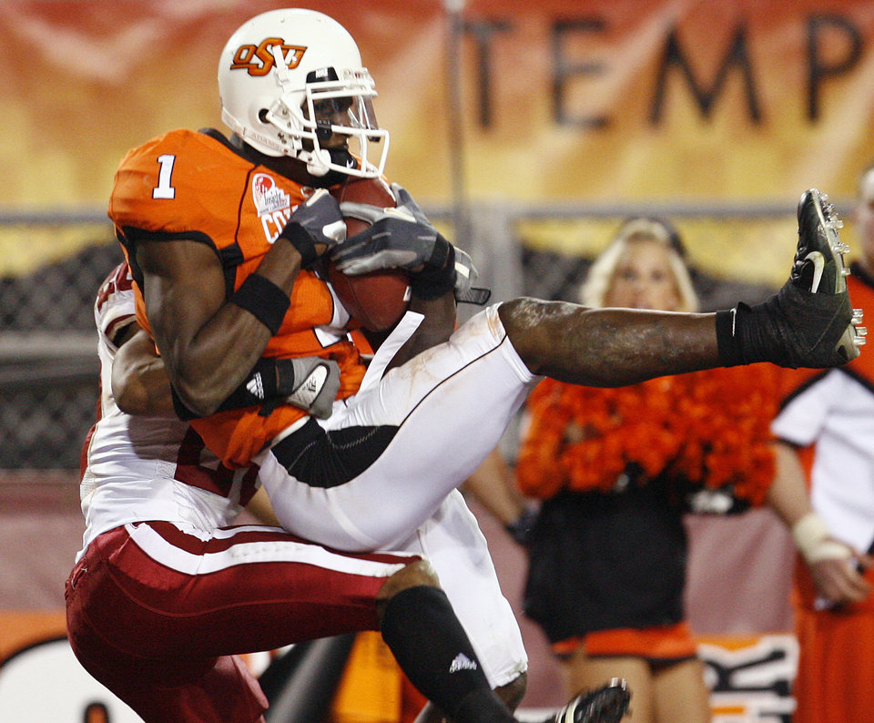 Photo - Oklahoma State's Dez Bryant (1) pulls in a touchdown pass over Indiana's Leslie Majors (28) during second half of the Insight Bowl college football game between Oklahoma State University (OSU) and the Indiana University Hoosiers (IU) at Sun Devil Stadium on Monday, Dec. 31, 2007, in Tempe, Ariz. 