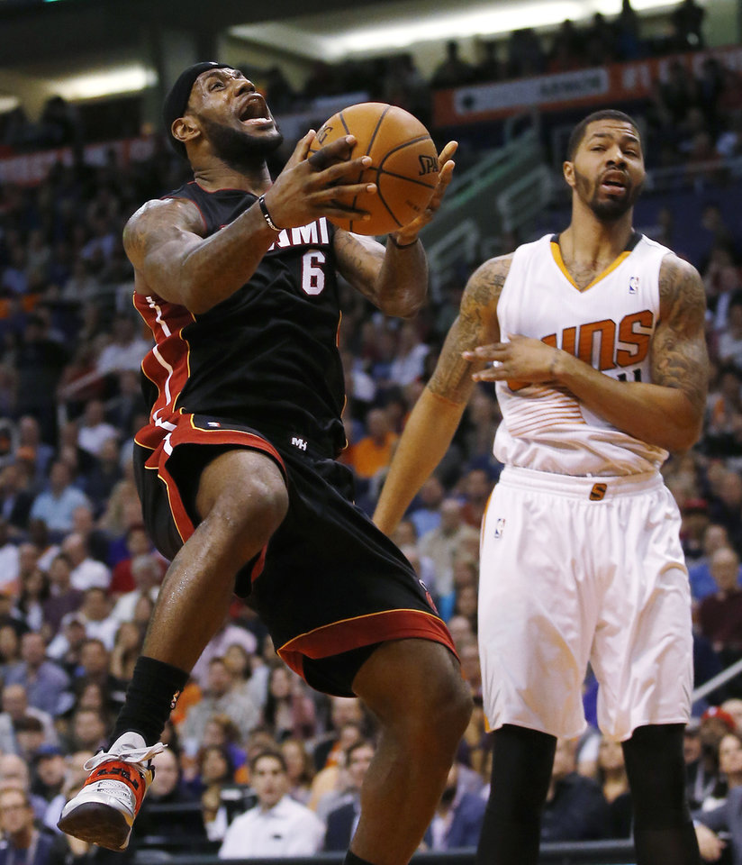 Photo - Miami Heat forward LeBron James is fouled by Phoenix Suns forward Markieff Morriss during the first half of an NBA basketball game Tuesday, Feb. 11, 2014, in Phoenix. (AP Photo/The Arizona Republic, Michael Chow) MAGS OUT  NO SALES  MESA OUT  MARICOPA COUNTY OUT