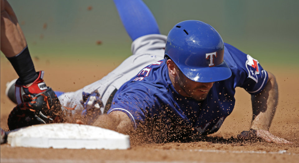 Photo - Texas Rangers' Adam Rosales dives safe back to first as Cleveland Indians first baseman Nick Swisher applies the tag during the fifth inning of a spring exhibition baseball game Tuesday, March 25, 2014, in Goodyear, Ariz. (AP Photo/Darron Cummings)