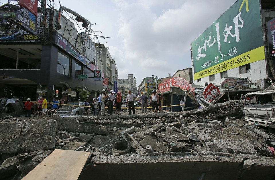 Photo - Locals survey the damage from massive gas explosions in Kaohsiung, Taiwan, Friday, Aug. 1, 2014. Scores of people were killed when several underground gas explosions ripped through Taiwan's second-largest city overnight, hurling concrete through the air and blasting long trenches in the streets, authorities said Friday. (AP Photo/Wally Santana)