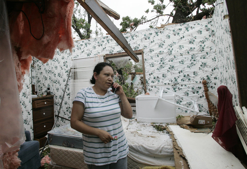 Photo - Yolanda Suarez talks on her cell phone in what is left of the bedroom of her mobile home in Seminole, Okla., Tuesday, May 11, 2010. Several tornadoes swept through Oklahoma on Monday, leaving a path of destruction, including Suarez's home. (AP Photo/Sue Ogrocki) ORG XMIT: OKSO102