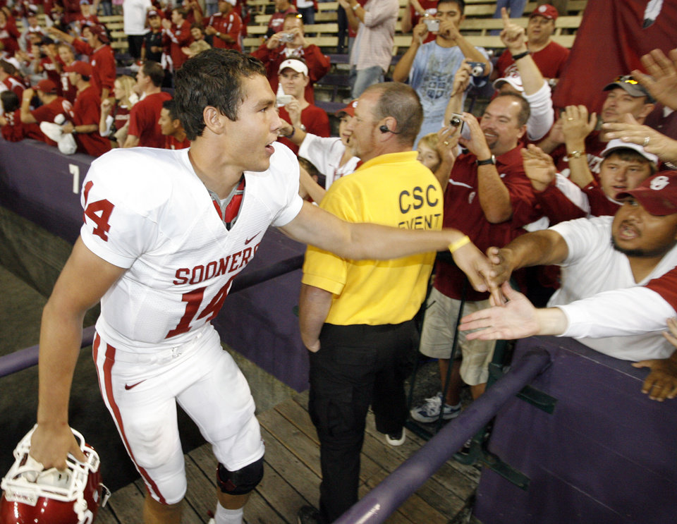 Photo - OU quarterback Sam Bradford (14) slaps hands with OU fans after the college football game between Oklahoma and Washington at Husky Stadium in Seattle, Wash., Saturday, September 13, 2008. OU beat UW, 55-14. BY NATE BILLINGS, THE OKLAHOMAN