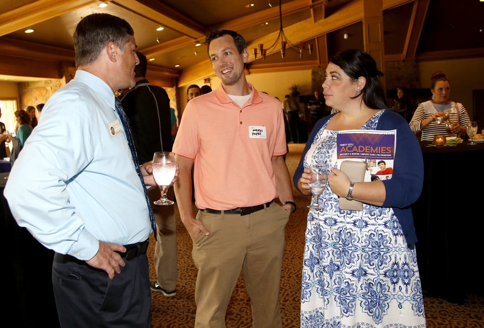 Photo -  Edmond North High School Principal Jason Pittenger, left, talks with Edmond North teacher Katie Dupre and her husband, Norris Dupre, during the Edmond Area Chamber of Commerce new teacher reception. [PHOTO BY BRYAN TERRY, THE OKLAHOMAN]