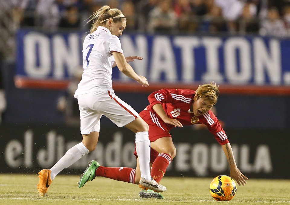 Photo - U.S. midfielder Morgan Brian sends China forward Li Ying to the ground during the first half of an international friendly soccer match, Thursday, April 10, 2014, in San Diego. (AP Photo/Lenny Ignelzi)
