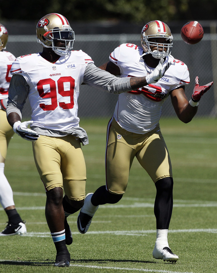 Photo -   FILE - In this Aug. 7, 2012, file photo, San Francisco 49ers linebackers Aldon Smith (99) and Ahmad Brooks (55) reach for the ball during NFL football practice in Santa Clara, Calif. They are not only the biggest reason behind the 49ers' defensive success, they are a close bunch that has quickly become the new NFL standard for linebackers. Meet Patrick Willis, NaVorro Bowman, Aldon Smith and Ahmad Brooks. (AP Photo/Jeff Chiu, File)