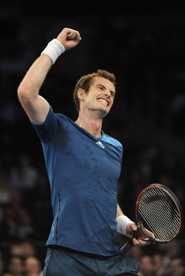 Photo - Andy Murray reacts to play against former Wimbledon champion Marion Bartolli who stepped onto the court to volley against Murray during the match against Novak Djokovic in the BNP Paribas Showdown Tennis Tournament on Monday, March 3, 2014, in New York. (AP Photo/Kathy Kmonicek)