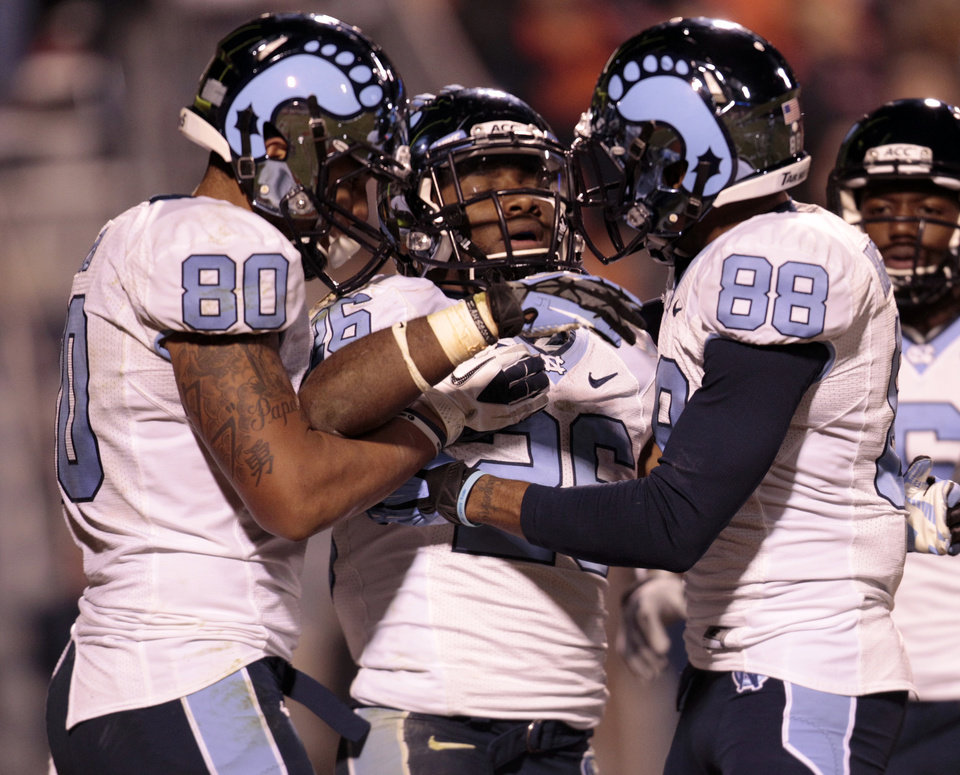 Photo -   North Carolina running back Giovani Bernard (26) celebrates a touchdown with teammates Jack Tabb (80) and Erik Highsmith (88) and during the second half of an NCAA college football game at Scott stadium Thursday, Nov. 15, 2012 in Charlottesville, VA. North Carolina won the game 37-13. (AP Photo/Steve Helber)