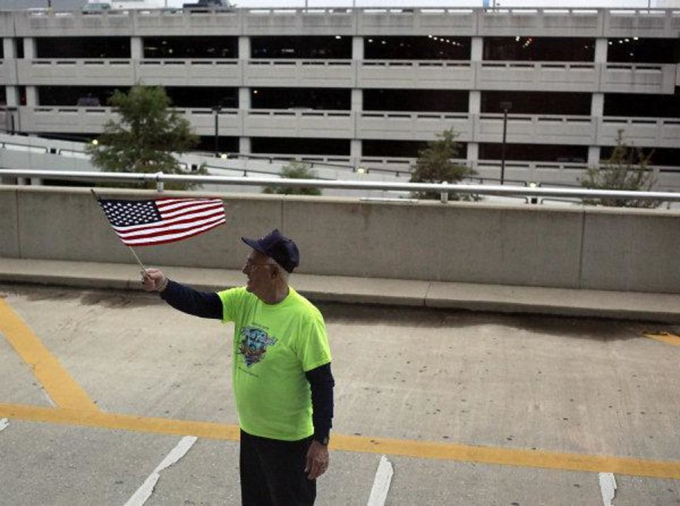 Photo - Seen from the bus window, a member of the Honor Flight Network's Baltimore Ground Crew waves a flag for WWII veterans from Oklahoma as they pull away from Baltimore Washington International Airport in Baltimore Maryland on Wednesday, Oct. 12, 2011. Veterans from WWII visited memorials in Washington D.C. and Virginia during an Oklahoma Honor Flight on Wednesday. Photo by John Clanton, The Oklahoman ORG XMIT: KOD