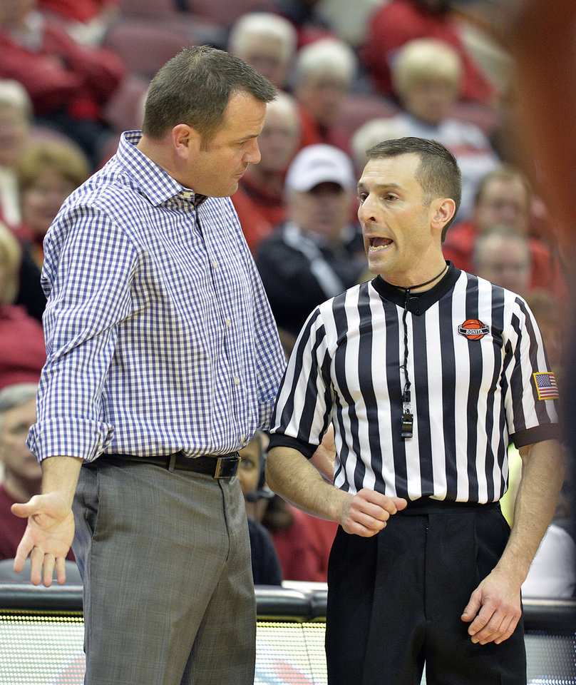 Photo - Louisville head coach Jeff walz, left, argues a call with referee Joseph Vaszily during the second half of an NCAA college basketball game on Wednesday, Jan. 15, 2014, in Louisville, Ky. Louisville defeated UCF 75-56. (AP Photo/Timothy D. Easley)