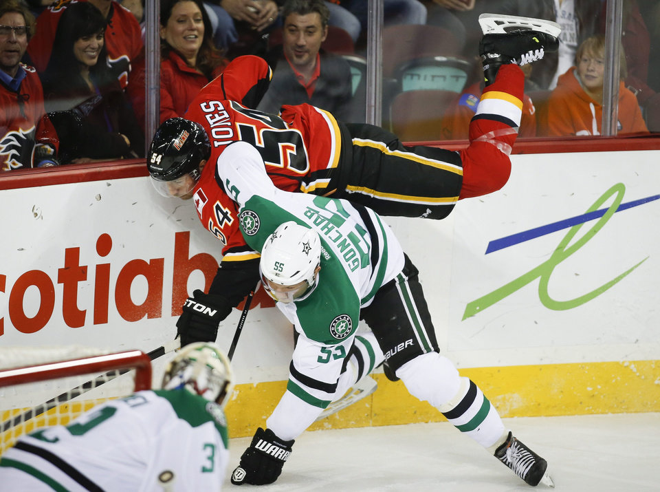 Dallas Stars' Sergei Gonchar, right, from Russia, upends Calgary Flames' David Jones during first-period NHL hockey game action in Calgary, Alberta., Thursday, Nov. 14, 2013. (AP Photo/The Canadian Press, Jeff McIntosh)