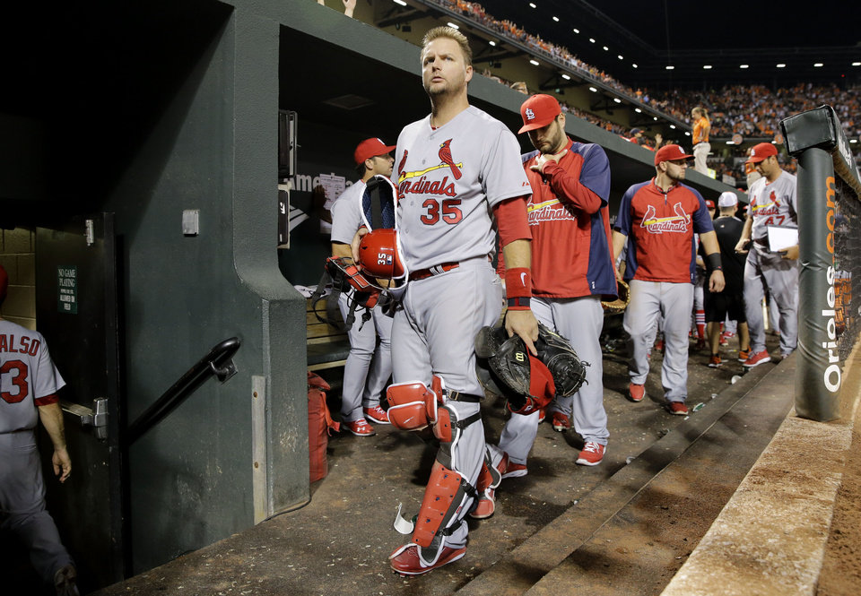Photo - St. Louis Cardinals catcher A.J. Pierzynski, center, heads to the clubhouse after an interleague baseball game against the Baltimore Orioles, Friday, Aug. 8, 2014, in Baltimore. Baltimore won 12-2. (AP Photo/Patrick Semansky)