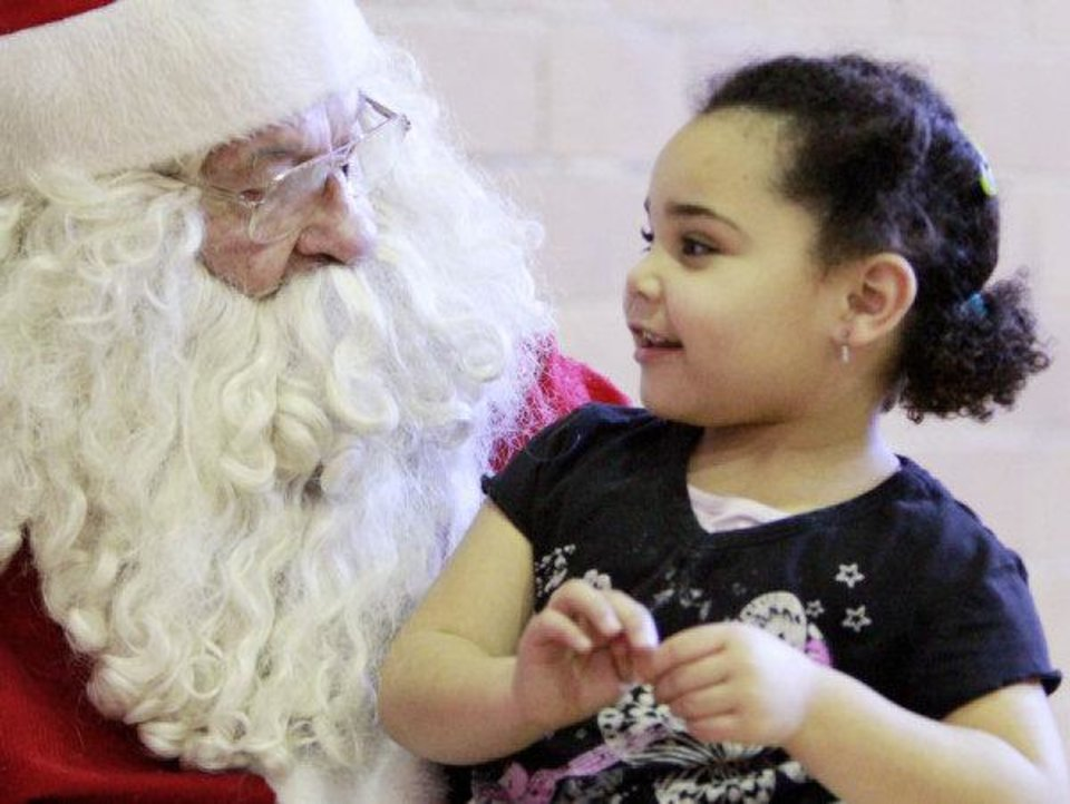 Photo - Hannah Parker, 5, talks with Santa on Friday afternoon at the City Rescue Mission.