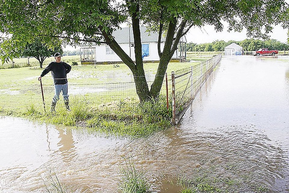 Photo - Rural resident Rodney Miller watches Monday as floodwaters flow near his home southwest of Ponca City. Miller's home sits just east of Bois d'Arc Creek.  Photo by Rolf Clement, Ponca City News