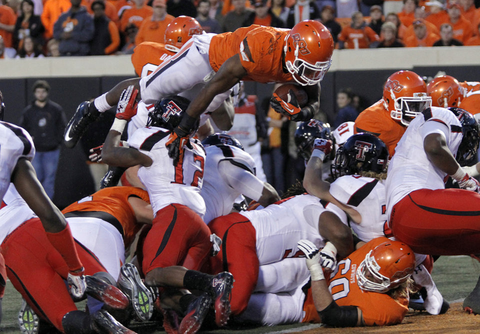 Photo - Oklahoma State's Joseph Randle (1) leaps over the line of scrimmage for a touchdown during the college football game between the Oklahoma State University Cowboys (OSU) and Texas Tech University Red Raiders (TTU) at Boone Pickens Stadium on Saturday, Nov. 17, 2012, in Stillwater, Okla.   Photo by Chris Landsberger, The Oklahoman