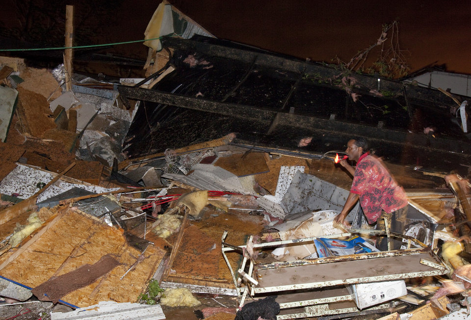 Photo -   A man listens for the sound of trapped people in the Pinaire mobile home park in Wichita,Kansas after a tornado cause massive destruction in the area on Saturday night April 14, 2012. Tornadoes were spotted across the Midwest and Plains on Saturday as an outbreak of unusually strong weather seized the region, and forecasters sternly warned that