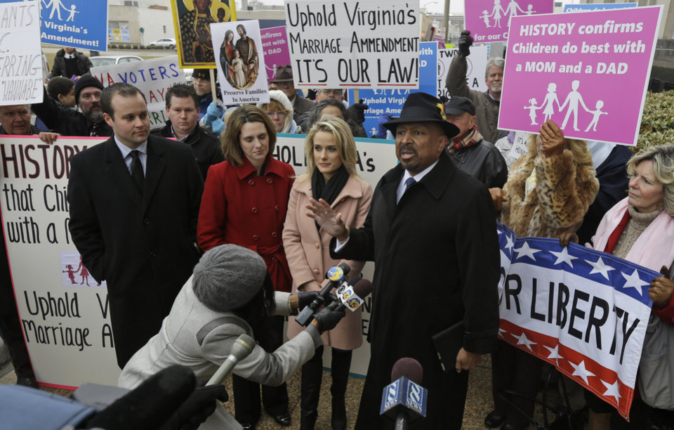 Photo - Former Republican lieutenant governor candidate E.W. Jackson, front right, speaks to the media during a demonstration outside federal court in Norfolk, Va., Tuesday, Feb. 4, 2014. Jackson spoke in favor of the law banning same-sex marriage. A federal judge will hear arguments Tuesday on whether Virginia's ban on gay marriage is unconstitutional. The state's newly elected Democratic attorney general has already decided to side with the plaintiffs and will not defend the ban. (AP Photo/Steve Helber)