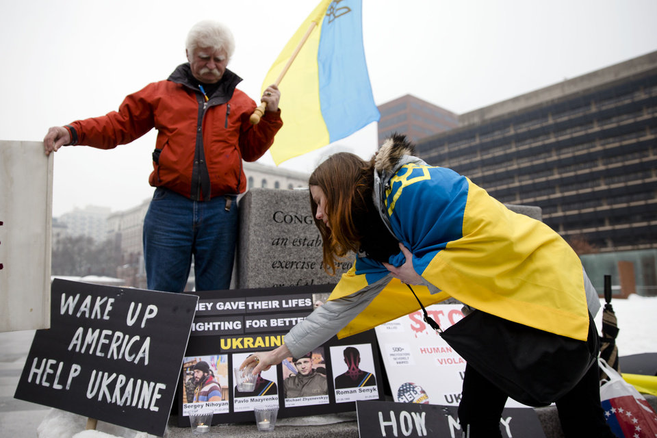 Photo - Yulia Kurka, places a candle as Basil Panczak looks on as they demonstrate in support Ukrainian anti-government protesters outside Independence Hall, Wednesday, Feb. 19, 2014, in Philadelphia. The violence on Tuesday was the worst in nearly three months of anti-government protests that have paralyzed Ukraine's capital, Kiev, in a struggle over the identity of a nation divided in loyalties between Russia and the West, and the worst in the country's post-Soviet history. (AP Photo/Matt Rourke)