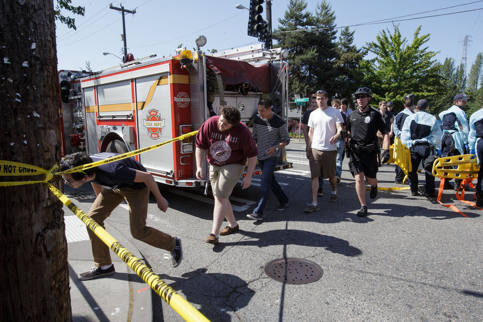 Photo - Seattle Pacific University students are lead out of the crime scene area after a shooting occurred on the university's campus Thursday, June 5, 2014, in Seattle. The university posted online Thursday that