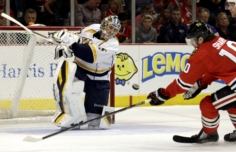 Photo - Nashville Predators goalie Pekka Rinne (35), left, blocks a shot by Chicago Blackhawks' Patrick Sharp (10) during the second period of an NHL hockey game in Chicago, Sunday, March 23, 2014. (AP Photo/Nam Y. Huh)