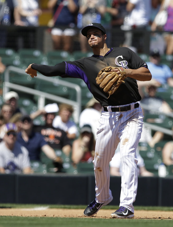 Photo - Colorado Rockies third baseman Nolan Arenado throws out Seattle Mariners' Abraham Almonte at first during the fourth inning of an exhibition baseball game Saturday, March 29, 2014, in Scottsdale, Ariz. (AP Photo/Darron Cummings)